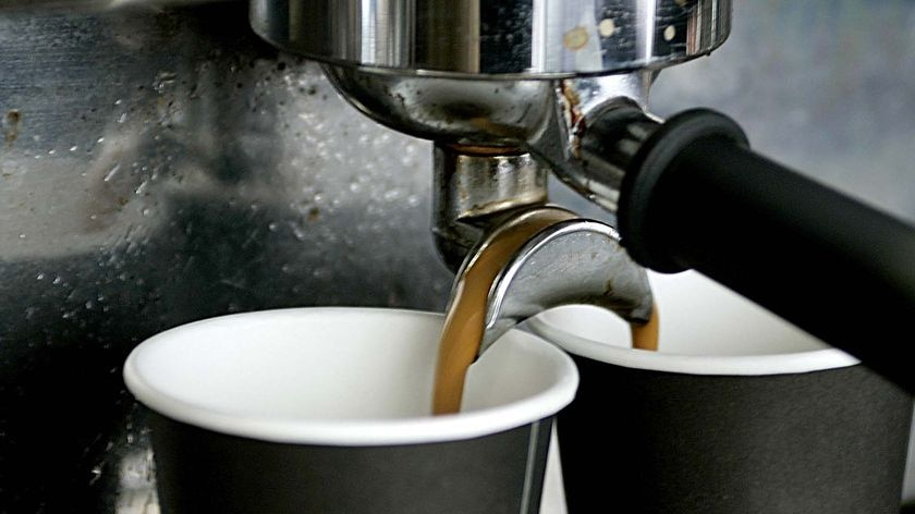 Coffee pours into cups from a machine at a coffee stand