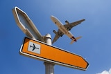 A plane flies past a sign pointing to an airport