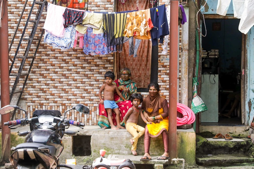 A grandmother, mother and two small children sit on a stoop under a line of washing