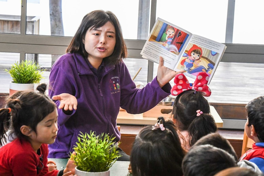 a woman in a purple jumper holds up a picture book with children infront of her