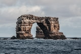 A rock in the ocean which has formed into a natural arch.