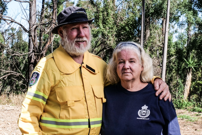Couple in RFS uniform standing on cleared property with with arms around each other