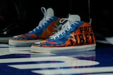 """A pair of basketball shoes coloured in with the words """"Free Tibet""""."""