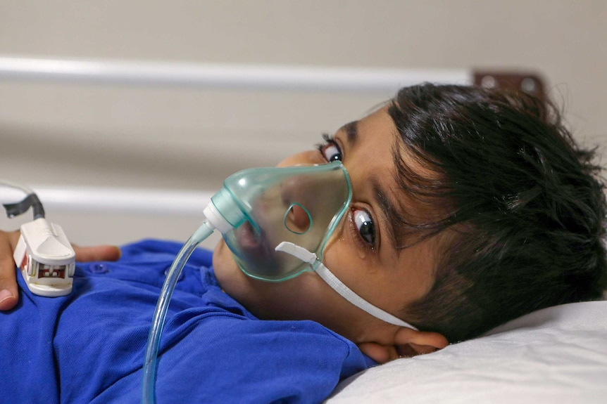A little boy with an oxygen mask on his face lying on a bed
