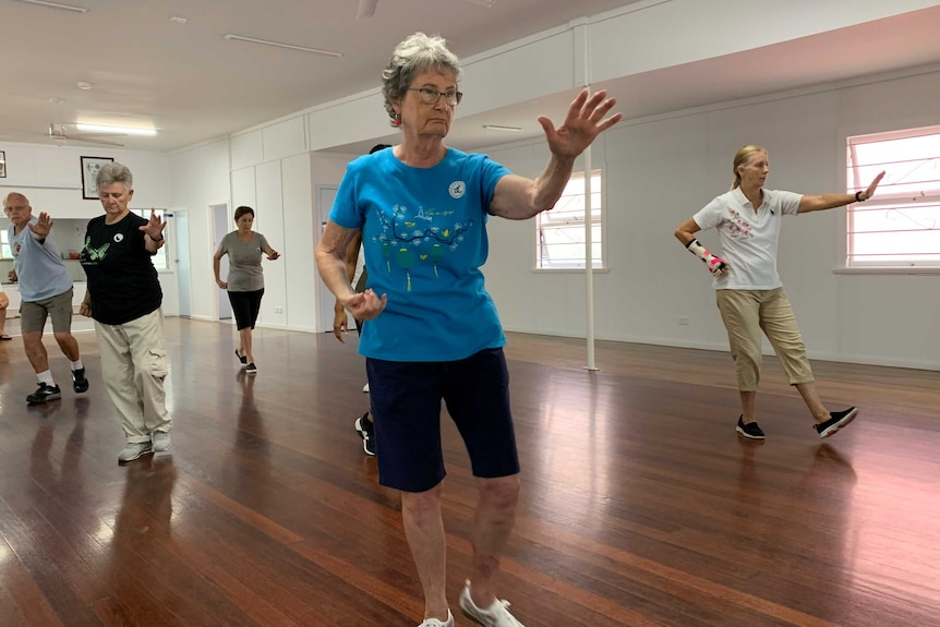 Arms outstretched as members of a tai chi class go through the motions in CWA hall