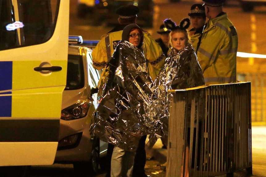 Two women wrapped in thermal blankets stand near the Manchester Arena in northern England, Britain