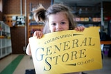 A little boy bites into a bright yellow sign with the words Colbinabbin General Store co-op written on it.