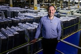 Man in shirt stands in front of mattresses at a mattress factory.