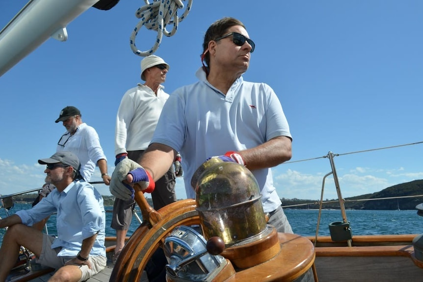 A man steers at a wooden helm.