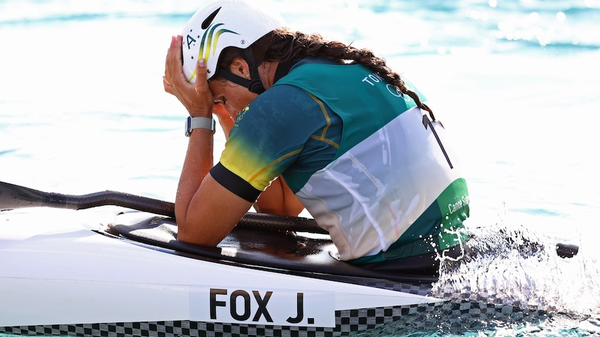 An Australian female kayaker in her canoe with her head in her hands.