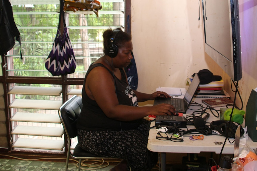 Belinda working at a desk in front of a laptop.