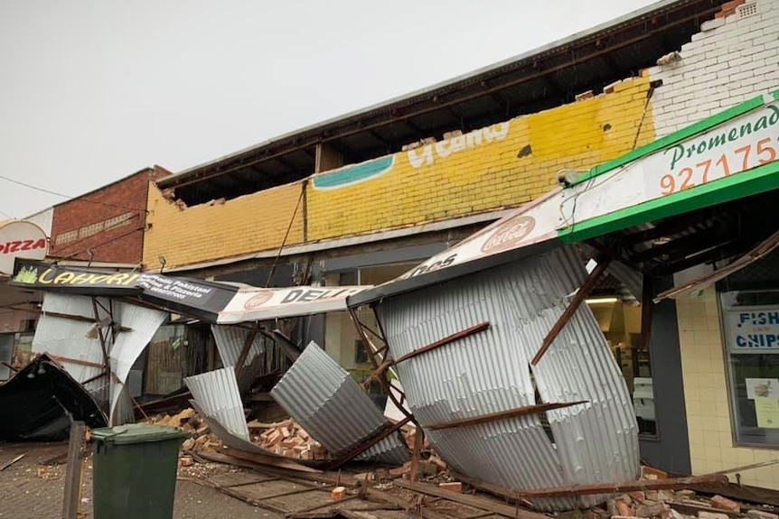 A row of shops with the front facade missing from storm damage
