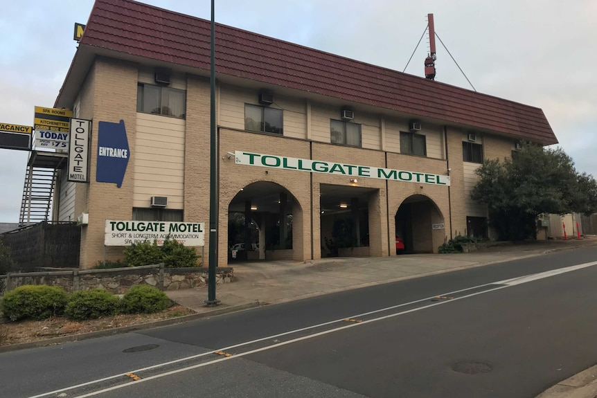 The photograph shows the exterior of a two-storey brick structure with a sign that reads Tollgate Motel.