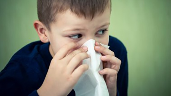 Boy blowing nose.