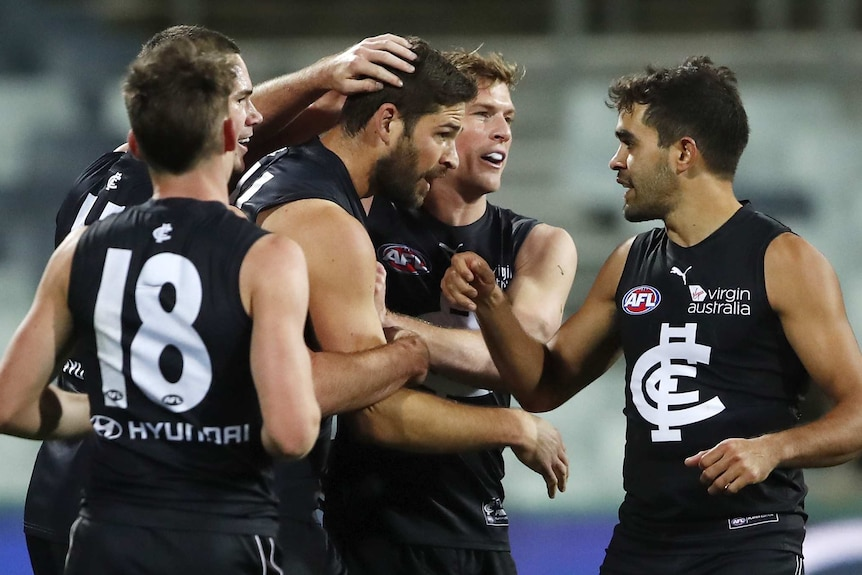 An AFL player gets patted on the head and back by teammates after his goal.