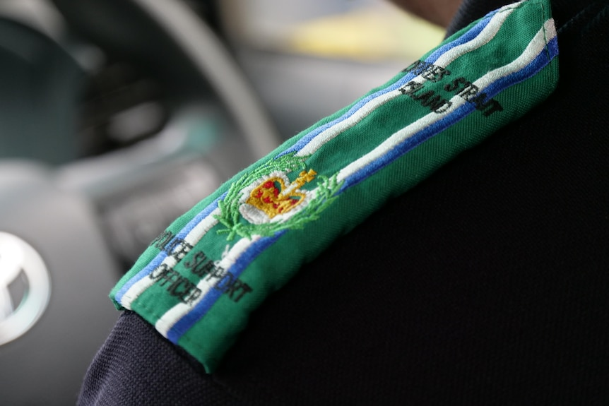 """A close-up of a blue police uniform epaulets howing the colours of the Torres Strait flag and the words """"Police Support Officer"""""""