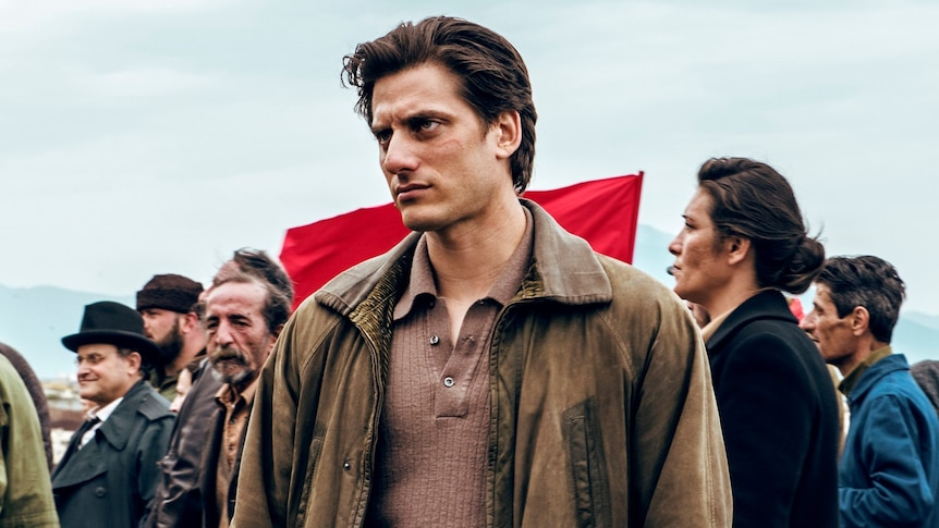 Luca Marnelli stands looking determined in front of a crowd of people carrying a red flag in Martin Eden