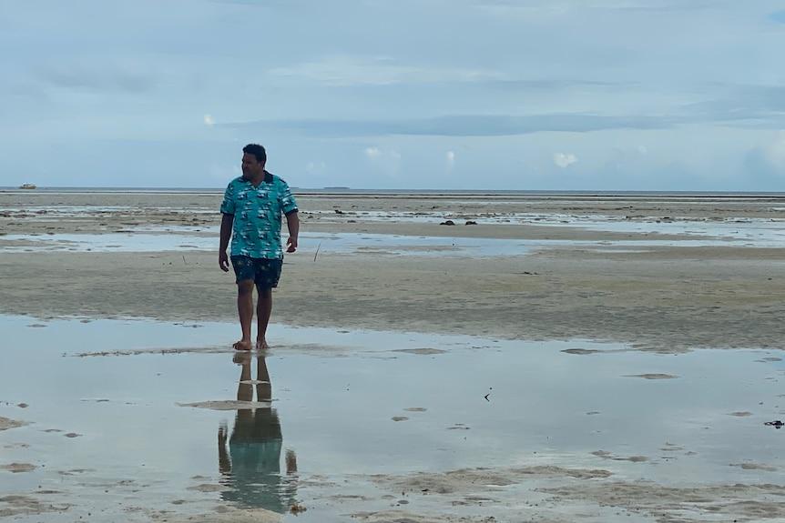Man in blue shirt and shorts walks along the beach.