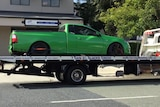 Seized green utility on back of flat bed tow truck.