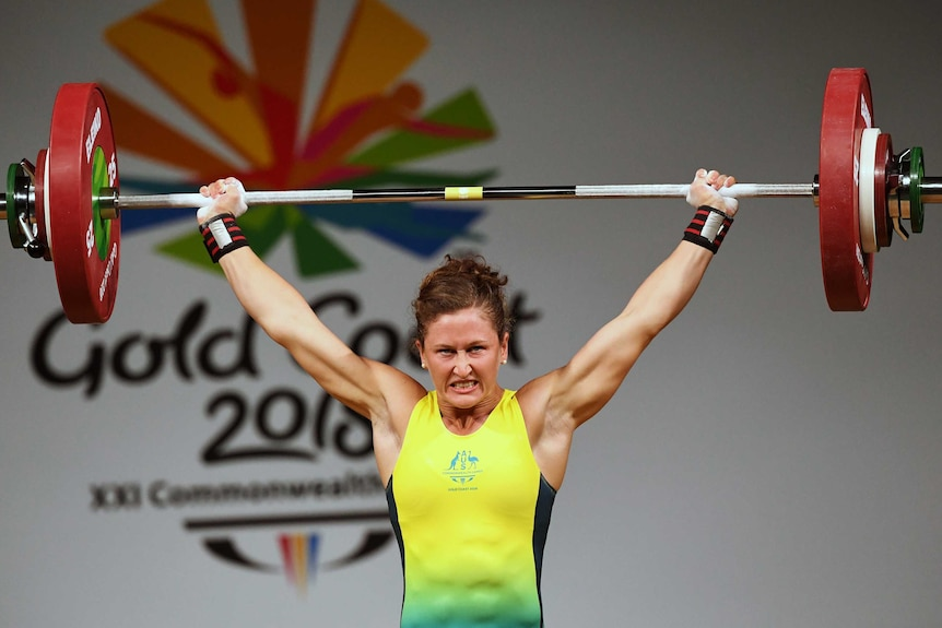 Tia-Clair Toomey holds a barbell over her head.