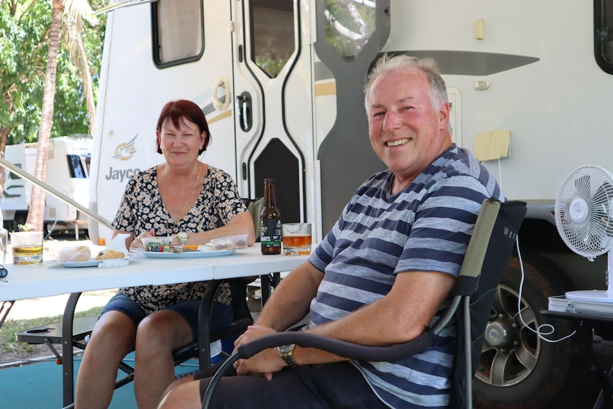Chris and Yvonne Roff are smiling as they sit at the table next to their van.