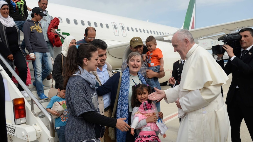 Pope Francis welcomes a groups of refugees disembarking from a plane in Rome.