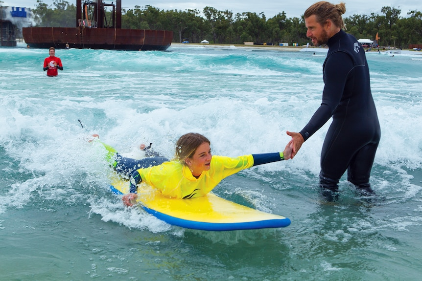 A young girl high high-fives a man in a wet suit as he prepares to stand up on a surfboard