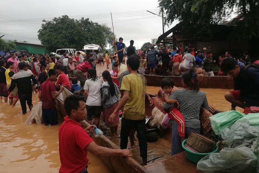 Crowds of people stand on boats in flooded streets.