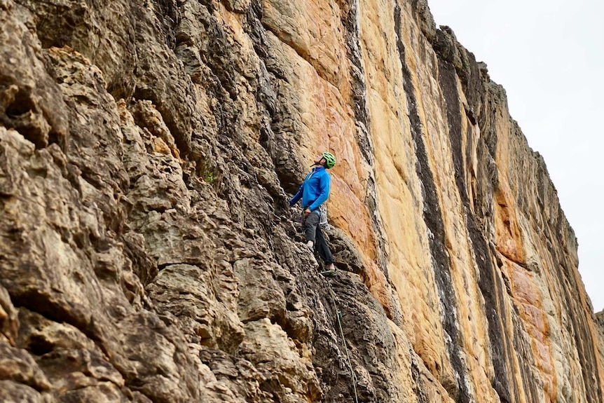 A man in a helmet climbs a sheer rock face with a rope and climbing gear