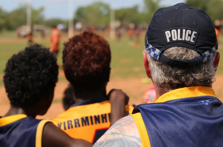 A police officer and two young men watch and AFL match.