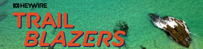 The word trailblazers is seen over a background of aqua sea with three rocks in the image. The word Heywire is seen at the top.