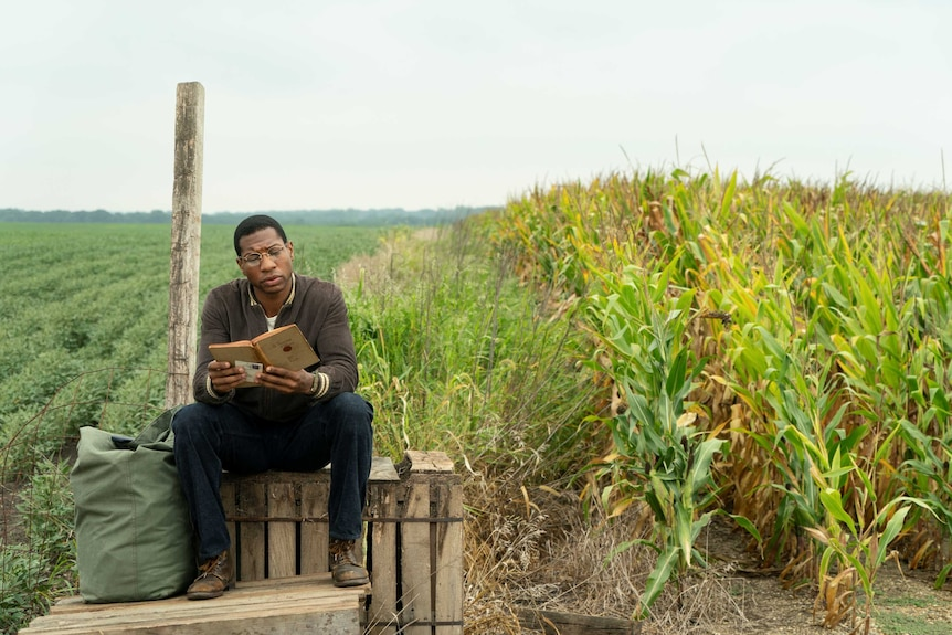 Actor Jonathan Major sitting on a wooden pallet reading a book surrounded by fields in 50s America in TV show Lovecraft Country