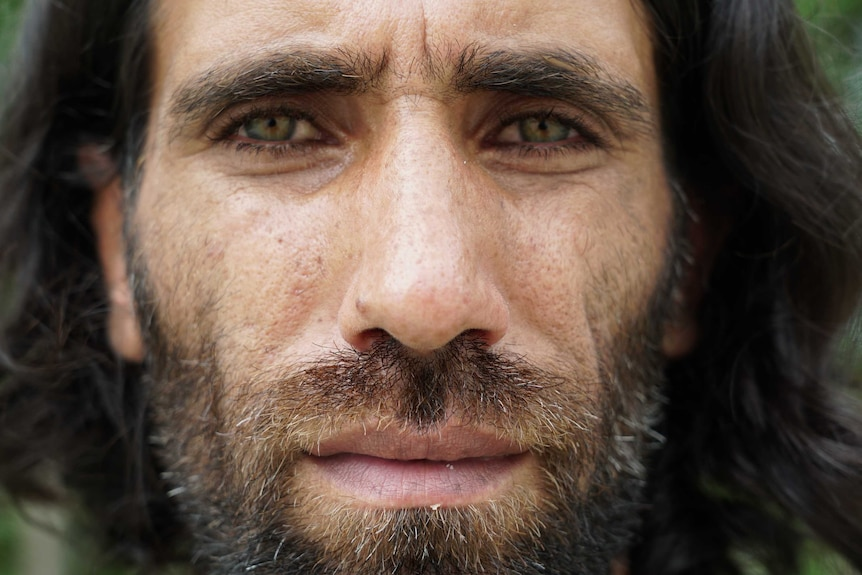 A close-up portrait of a man with a scruffy beard and piercing green eyes.