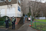 Police are seen outside the Alfred Street public housing tower.