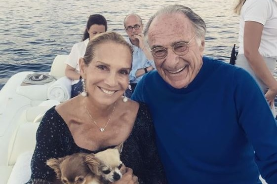 A smiling woman holding two dogs sitting never to a smiling man. They are aboard a yacht.