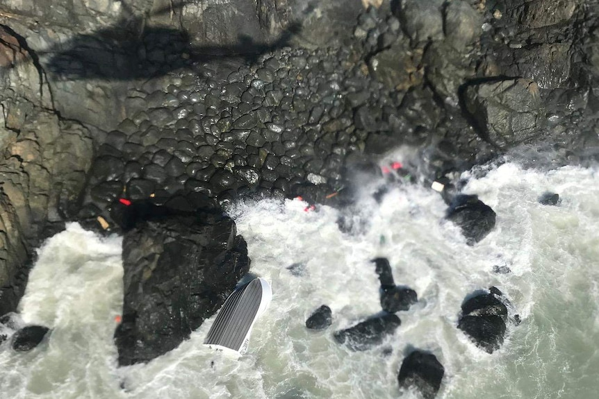 The rough sea smashes against rocks at a cliff base, where a capsized tinny floats