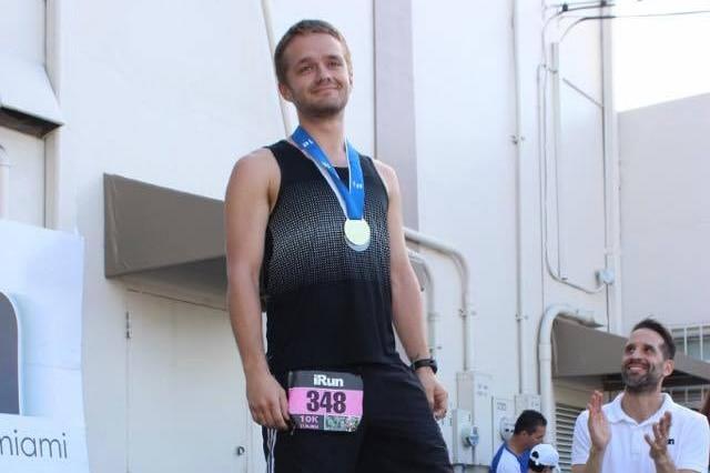 Matthew Dawson-Clarke wears a gold medal after winning a long distance race.