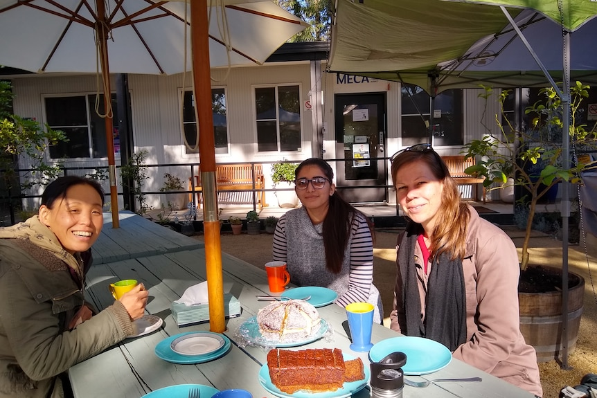 Three women at a picnic table sharing tea and cakes at a community garden in western Sydney.