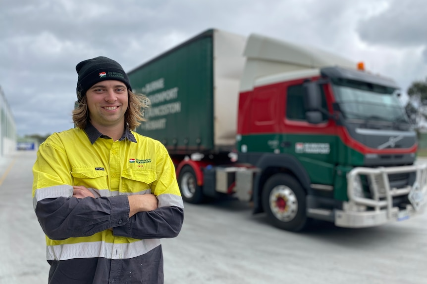 Tasmanian truck driver Tate Vanderfeen stands in front of his big parked truck.