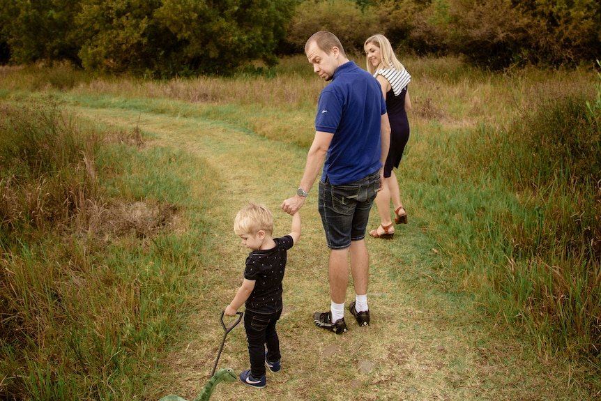 A man holds the hand of a small boy who is hauling a toy cart as they and a woman walk along a grassed path between scrub.