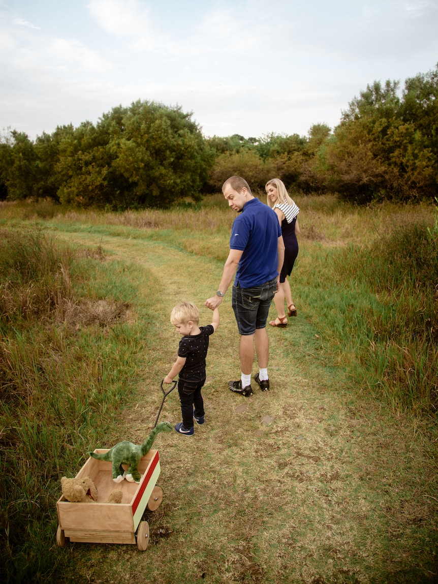 A man holds the hand of a little boy who pulls a toy cart as they and a woman walk along a grassy path between brushwood.