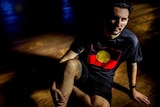 A shadowy  image of Robert McLellen wearing the Aboriginal flag