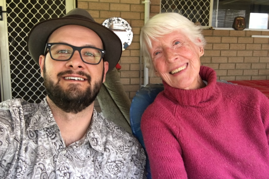 A close-up photo of Jordan Shields and Joy Denys sitting outside a house.