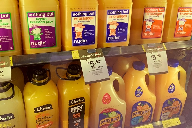 Large bottles of various brands of orange juice in a supermarket fridge