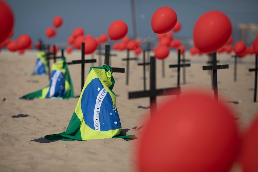 Crosses, red balloons and Brazilian nation flags appear on a beach in a demonstration to remember Brazil's coronavirus victims.