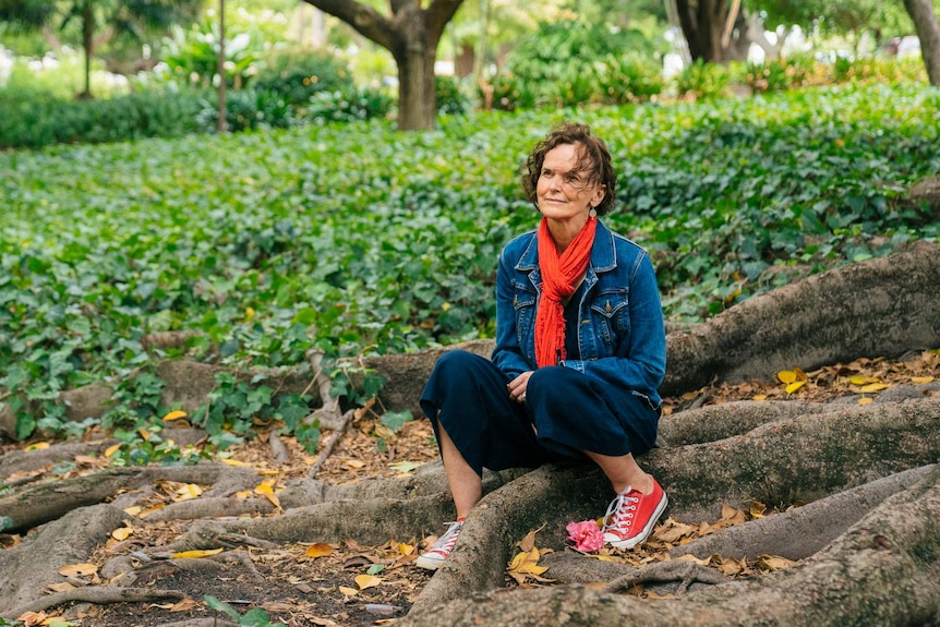 Andrea Hammond sits at the foot of a tree in a public garden in Perth.
