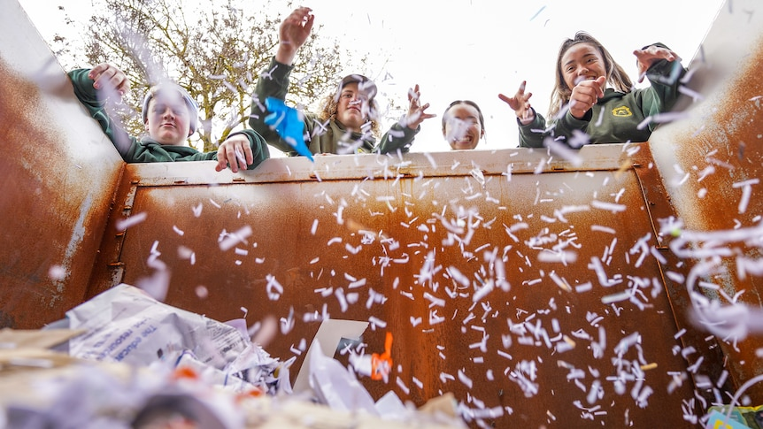 Four teenage students throw shredded paper into a skip bin, creating a falling snow affect.