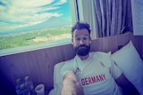 A man in a Germany jersey lying in a hotel room bed with a mountain view from his window