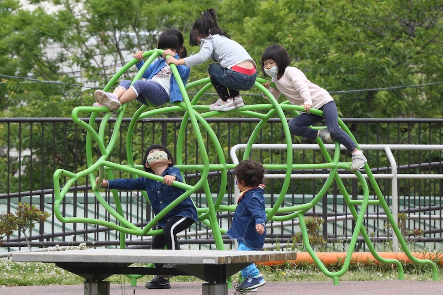 Kids in face masks climb over playground equipment