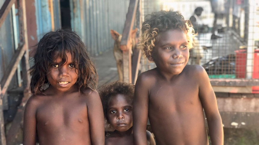 Three children look at the camera